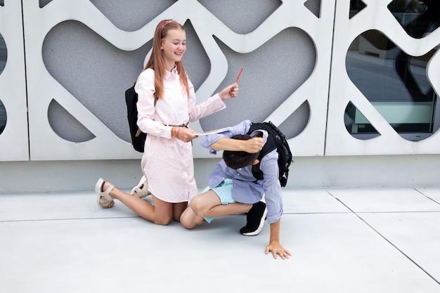 Dzieci nastolatki dzieci w wieku szkolnym chłopiec i dziewczynka na tle betonowej ściany dzieci śmieją się i bawią...