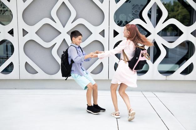 Dzieci nastolatki dzieci w wieku szkolnym chłopiec i dziewczynka na tle betonowej ściany dzieci śmieją się i ...