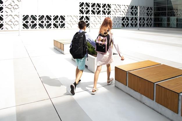 Dzieci nastolatki dzieci w wieku szkolnym chłopiec i dziewczynka na tle betonowej ściany z plecakami trzymają ha...