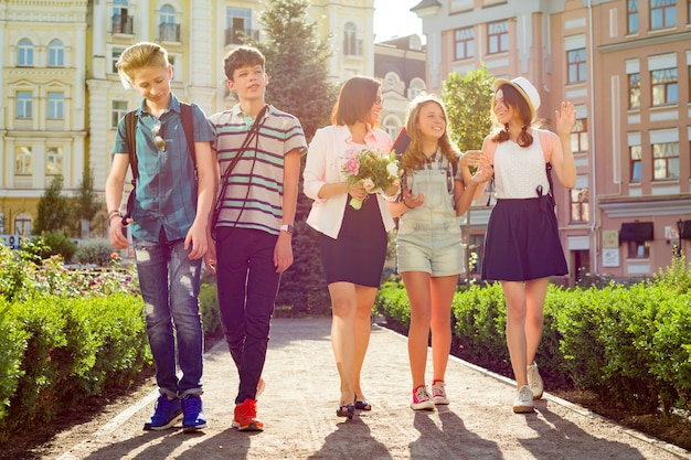 Dzieci nastolatki idą ze swoim nauczycielem