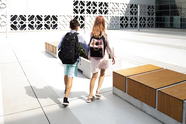 Dzieci nastolatki uczniowie chłopiec i dziewczynka na tle betonowej ściany idą do budynku szkolnego ...