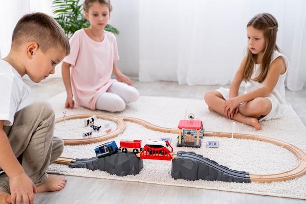Dzieci niebinarne bawiące się samochodami w pomieszczeniu