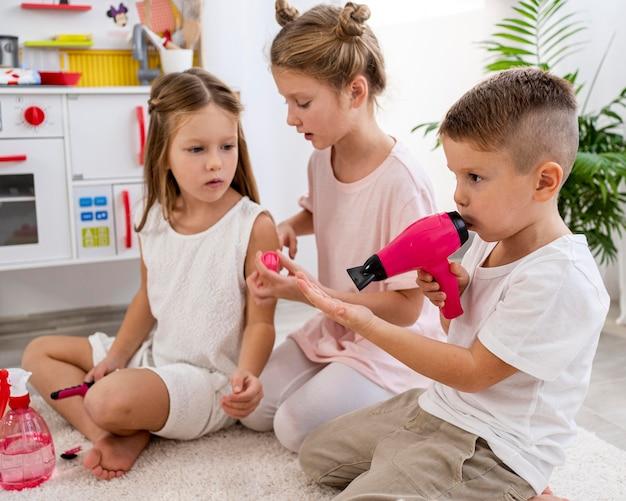 Dzieci niebinarne grające razem w salon piękności