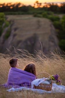 Dzieci o zachodzie słońca siedzą na pikniku.