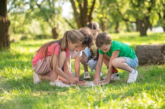 Dzieci odkrywają mapę na zielonym trawniku