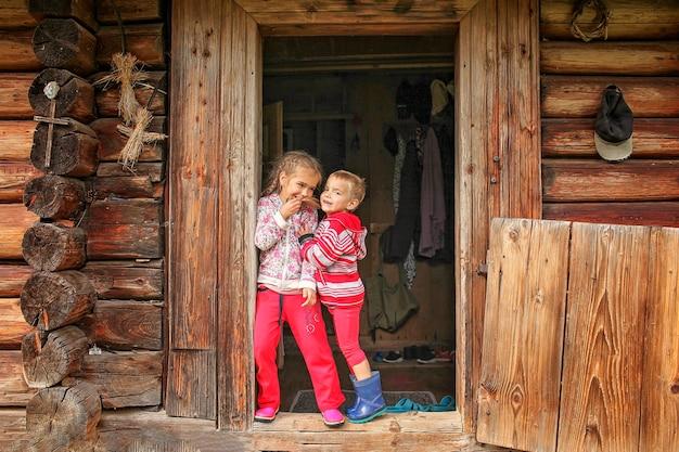 Dzieci odpoczywające na progu starego drewnianego domu podczas letnich wakacji, ekologiczna koncepcja podróży
