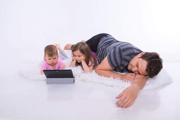 Dzieci oglądają bajki na tablecie. śpi mężczyzna. urlop rodzinny, wspólna rozrywka. rodzice z dziewczynami na podłodze