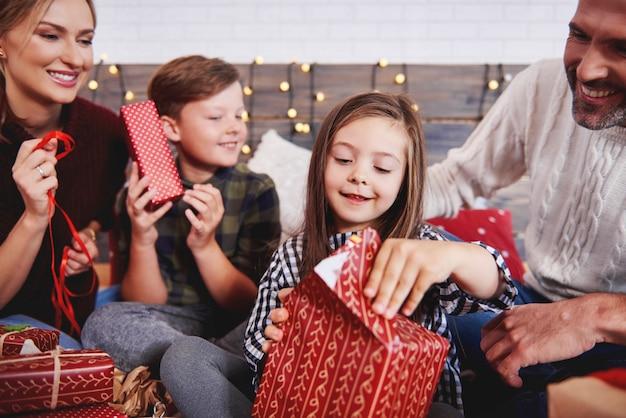 Dzieci otwierają prezent bożonarodzeniowy z rodzicami