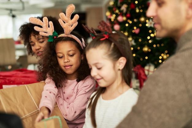 Dzieci otwierają prezenty świąteczne z rodzicami