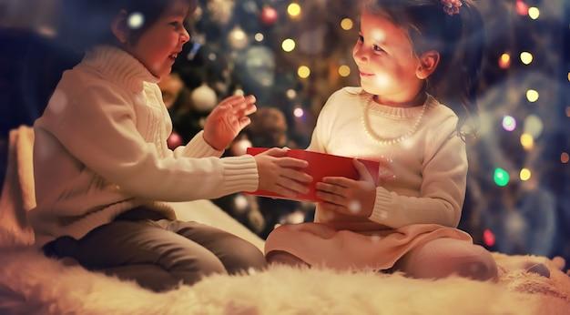 Dzieci otwierające prezenty świąteczne dzieci pod choinką z pudełkami na prezenty