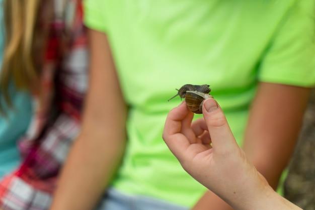 Dzieci patrzą razem na ślimaka