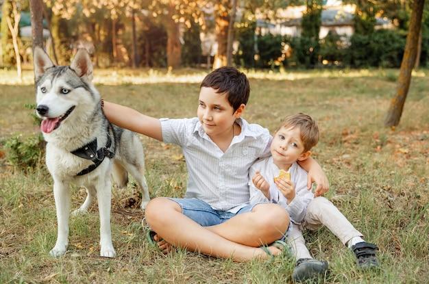 Dzieci pieszczą psa na zewnątrz. właściciel spaceruje z psem. rodzina gra z psem w parku. dzieci i zwierzak na letniej łące.