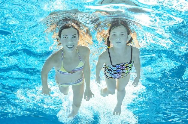 Dzieci pływają pod wodą w basenie, szczęśliwe aktywne dziewczyny bawią się pod wodą