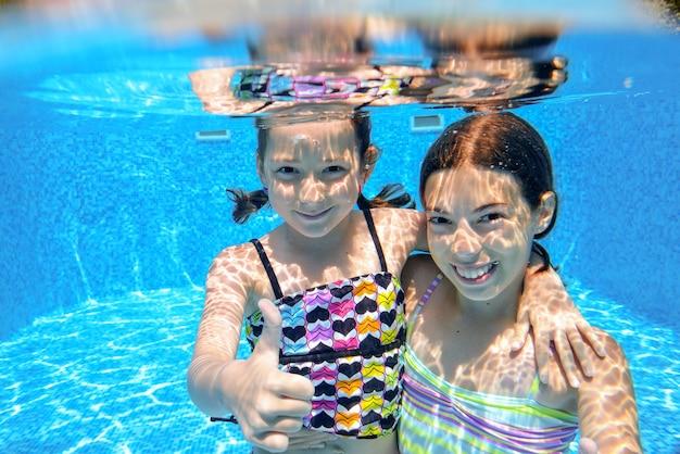 Dzieci pływają w basenie pod wodą, szczęśliwe aktywne dziewczyny bawią się pod wodą, dzieci bawią się na wakacjach rodzinnych