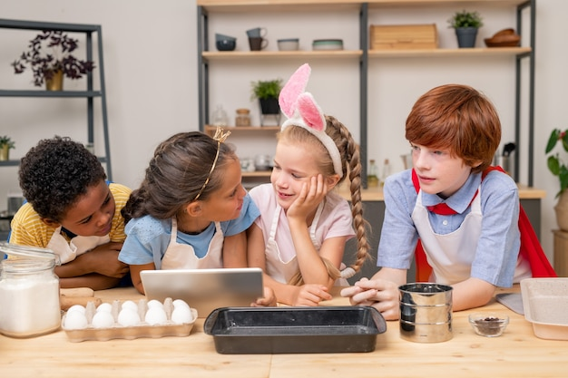 Dzieci pochłonięte czytaniem przepisu za pomocą cyfrowego tabletu stojąc przy drewnianym stole w kuchni, aby zrobić niespodziankę na dzień matki