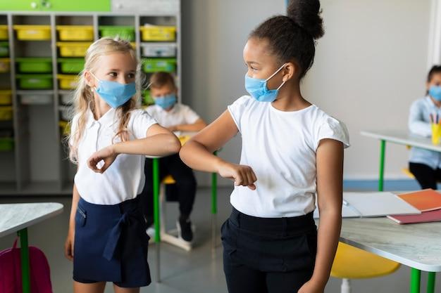 Dzieci podbijają łokieć w klasie