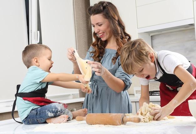 Dzieci pomagają młodej matce w wyrabianiu ciasta