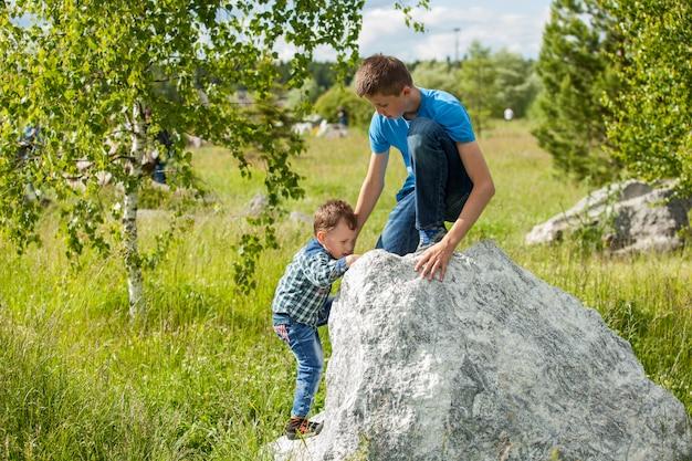 Dzieci pomagają sobie nawzajem wspinać się po skale