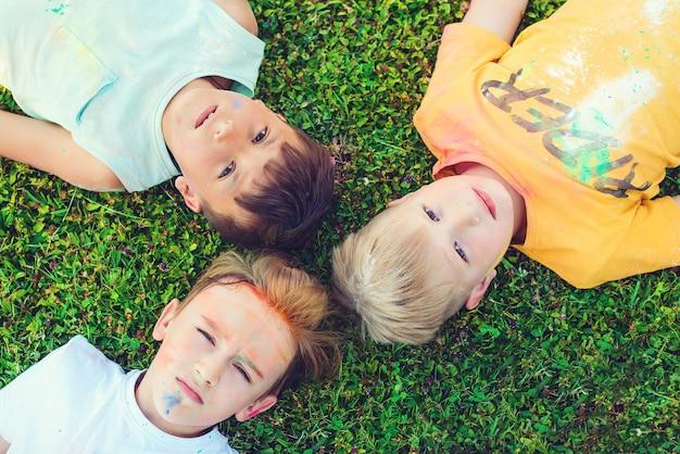 Dzieci pomalowane w barwach festiwalu holi. chłopcy leżą na zielonej trawie. święto holi. przyjaciele bawią się podczas święta holi. szczęśliwe dzieciństwo. pre teen chłopcy bawiący się kolorami.