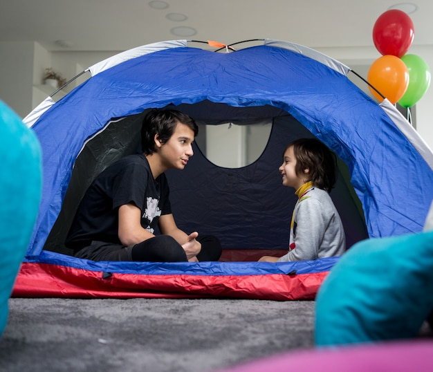 Dzieci posiadające namiot kempingowy w salonie dla zabawy i przygody