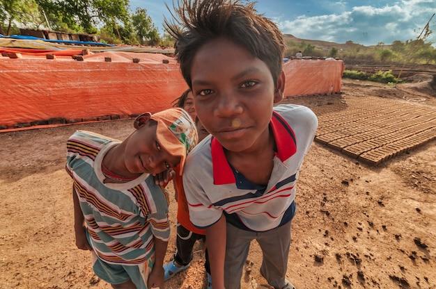 Dzieci pracowników pomagających w ręcznym wykonywaniu tradycyjnych cegieł w cegielni lub fabryce.