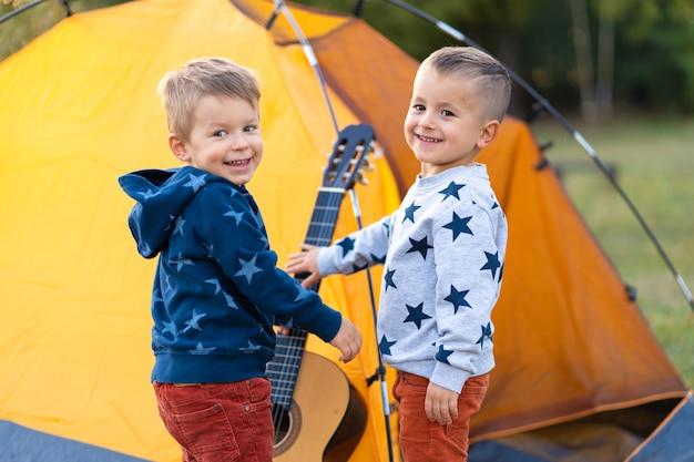 Dzieci proszą tatę, żeby grał na gitarze. camping z rodziną w lesie. szczęśliwy rodzinny weekend