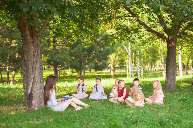 Dzieci prowadzą lekcję z nauczycielem w parku na zielonym trawniku.
