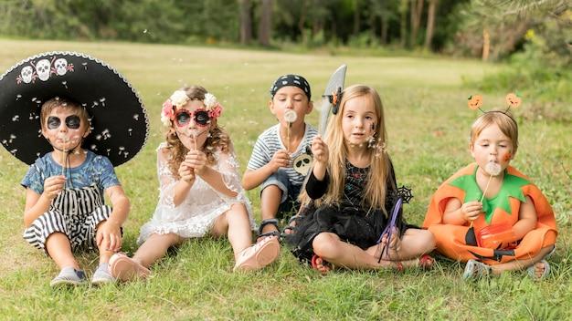 Dzieci przebrane na halloween siedzą na trawie