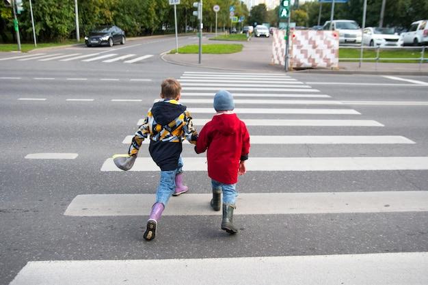 Dzieci przechodzą przez jezdnię przez przejście dla pieszych. pasy do przejścia zebry