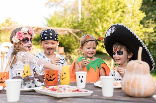 Dzieci przy stole z kostiumem na halloween
