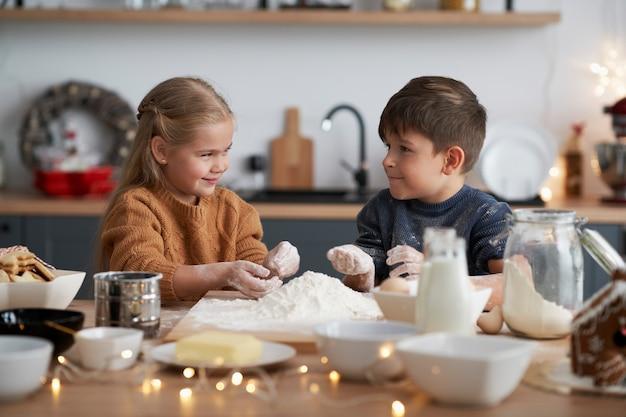 Dzieci przygotowują ciasto na świąteczne ciasteczka