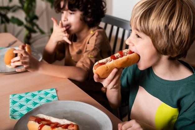 Dzieci razem jedzą hot dogi