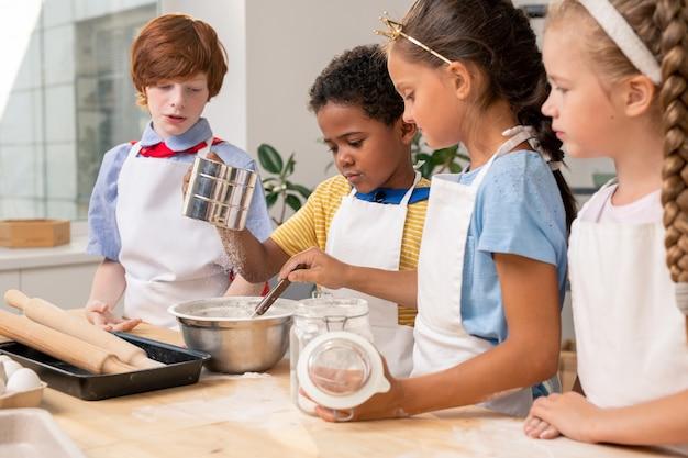 Dzieci razem nalewają ciasto, w fartuchach, patrząc na siebie z szerokim uśmiechem, przygotowując apetyczne ciasteczka dla rodziców