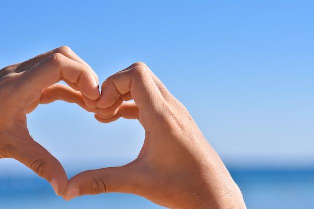 Dzieci ręki w piasku pokazują kierowego gest przeciw niebieskiemu niebu i morzu