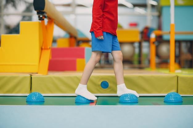 Dzieci robi masaż jeża do ćwiczeń nóg stóp na siłowni w przedszkolu lub szkole podstawowej. koncepcja sportu i fitness dzieci.