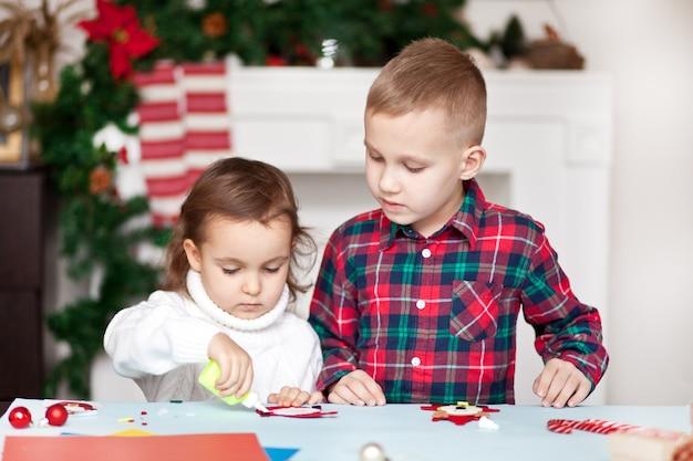 Dzieci robią dekoracje na choinkę lub prezenty. boże narodzenie ręcznie robiony projekt diy.