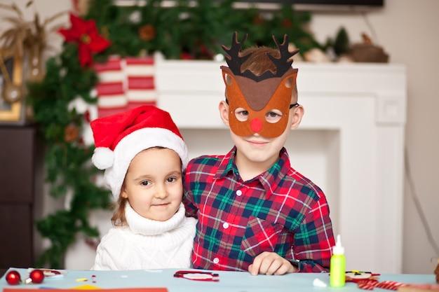 Dzieci robią dekoracje na choinkę lub prezenty.