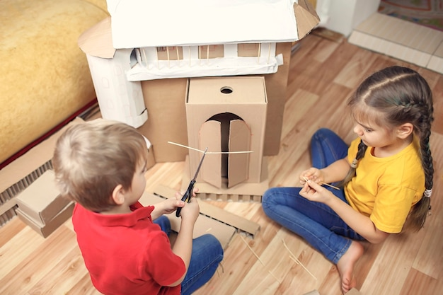Dzieci robią dom z papieru z tekturowym pudełkiem po dostawie online i wspólnej zabawie