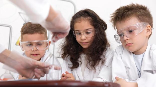 Dzieci robią eksperyment chemiczny w szkole