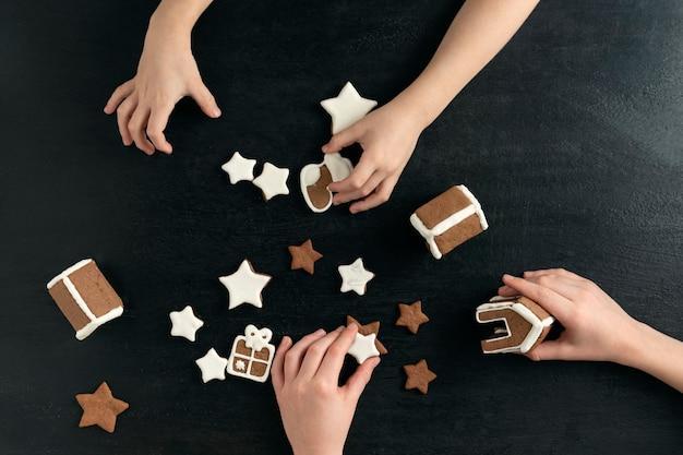 Dzieci robią pierniki. ręce dzieci i ciasteczka pierniki w cukrze na czarnym tle, widok z góry.