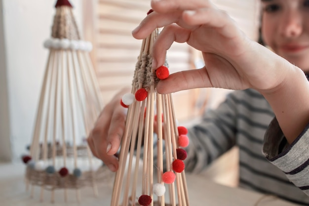 Dzieci robią ręcznie robioną choinkę z bambusowych patyczków wielokrotnego użytku ozdoba diy noworoczna dekoracja