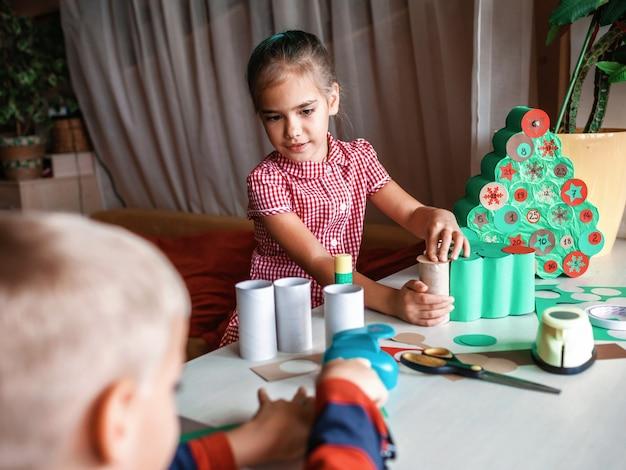 Dzieci robią ręcznie robiony kalendarz adwentowy z rolkami papieru toaletowego w domu