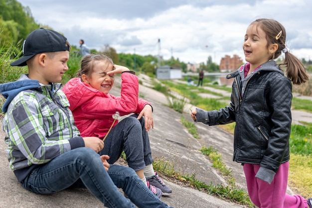 Dzieci rozmawiają o czymś siedząc na łonie natury z mleczem w dłoniach.