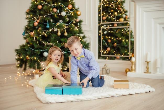 Dzieci rozpakowują prezenty świąteczne