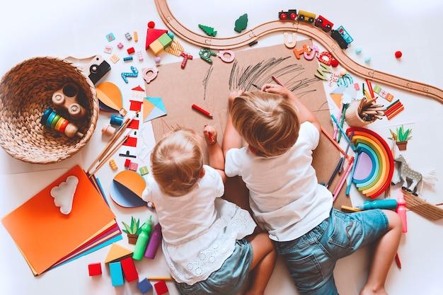 Dzieci rysują i wykonują rękodzieło. dzieci z zabawkami edukacyjnymi i przyborami szkolnymi dla kreatywności. tło dla przedszkola i przedszkola lub zajęć plastycznych. chłopiec i dziewczynka bawią się w domu lub przedszkolu