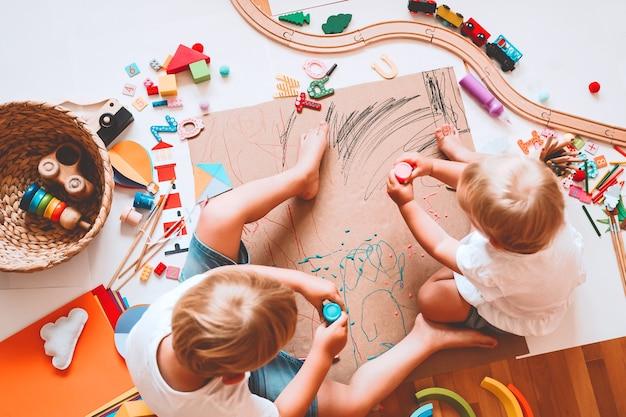 Dzieci rysują i wykonują rękodzieło dzieci z zabawkami edukacyjnymi i przyborami szkolnymi dla kreatywności