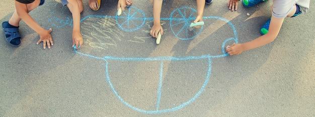 Dzieci rysują kredą samochód na chodniku.