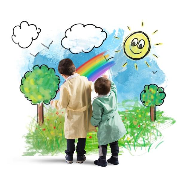 Dzieci rysują na ścianie kolorowy krajobraz