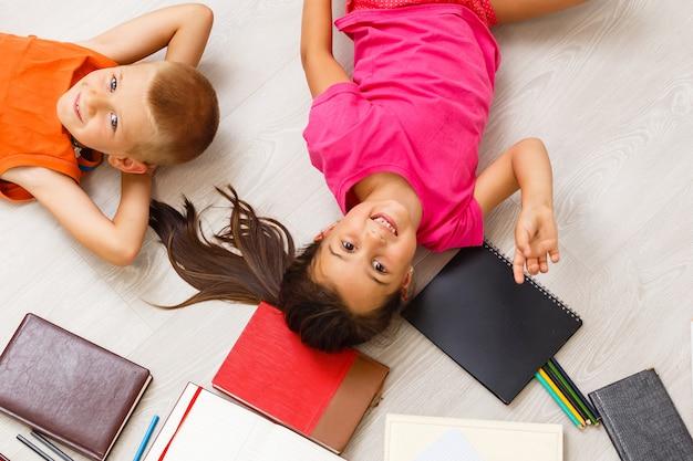 Dzieci rysunek na podłodze na papierze. chłopiec i dziewczynka w wieku przedszkolnym bawią się na podłodze zabawkami edukacyjnymi, klockami, pociągiem, koleją, samolotem. zabawki do przedszkola i przedszkola. dzieci w domu lub w przedszkolu. widok z góry