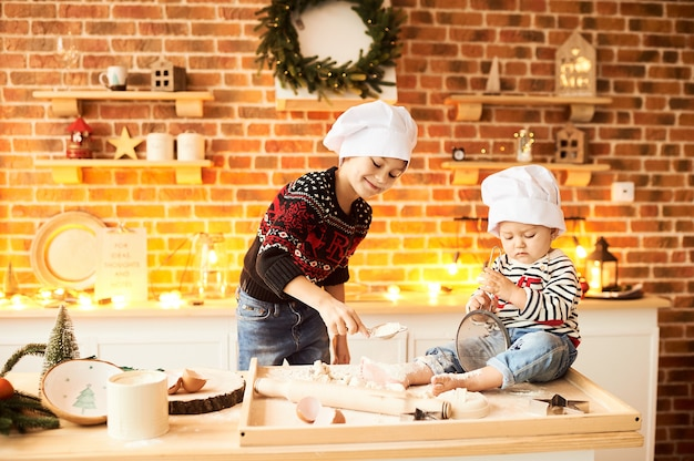 Dzieci są gotowane i bawione w kuchni mąką i ciastem